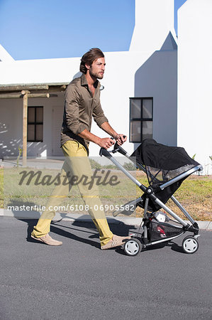 Man pushing a baby stroller on a road Stock Photo - Premium Royalty-Free, Image code: 6108-06905582