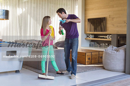 Father and daughter holding cleaning equipment and discussing Stock Photo - Premium Royalty-Free, Image code: 6108-06905592