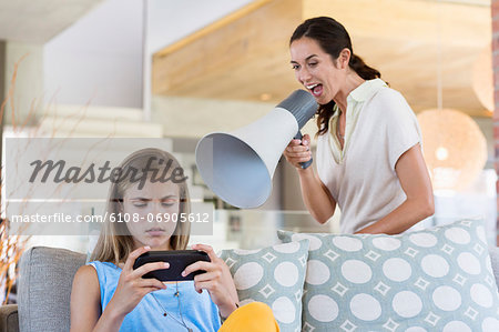 Woman shouting through a megaphone at his daughter for playing video game Stock Photo - Premium Royalty-Free, Image code: 6108-06905612