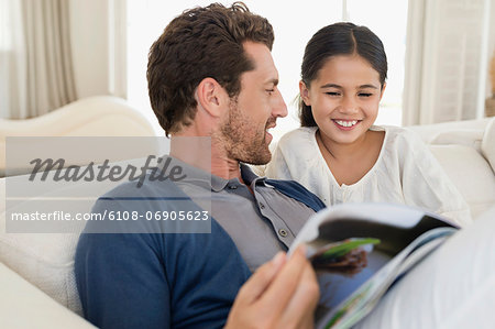 Man and his daughter reading a magazine Stock Photo - Premium Royalty-Free, Image code: 6108-06905623