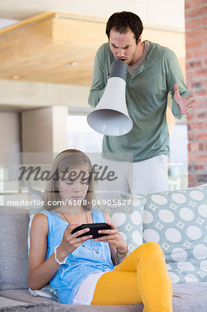 Man shouting into a megaphone at his daughter for playing video game Stock Photo - Premium Royalty-Free, Image code: 6108-06905627
