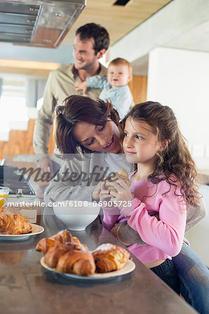 Girl having breakfast beside her mother at a kitchen counter Stock Photo - Premium Royalty-Free, Image code: 6108-06905725