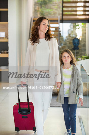 Woman walking with her daughter with a luggage Stock Photo - Premium Royalty-Free, Image code: 6108-06905731