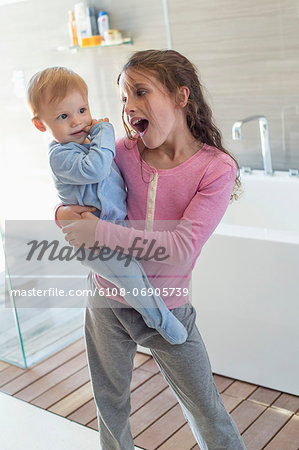 Girl carrying her brother and looking surprised in a bathroom Stock Photo - Premium Royalty-Free, Image code: 6108-06905739