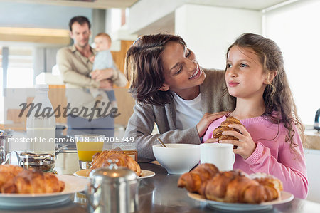 Girl having breakfast beside her mother at a kitchen counter Stock Photo - Premium Royalty-Free, Image code: 6108-06905749