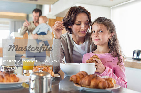 Girl having breakfast beside her mother at a kitchen counter Stock Photo - Premium Royalty-Free, Image code: 6108-06905763