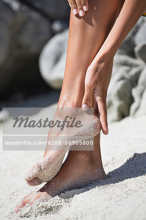 Woman cleaning sand of her feet Stock Photo - Premium Royalty-Free, Image code: 6108-06905800