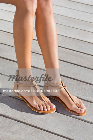 Low section view of a woman wearing sandals Stock Photo - Premium Royalty-Free, Image code: 6108-06905802