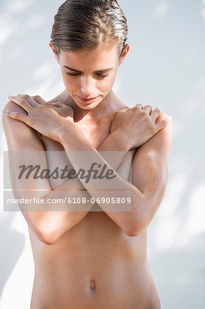 Woman hiding her breast with her hands Stock Photo - Premium Royalty-Free, Image code: 6108-06905809