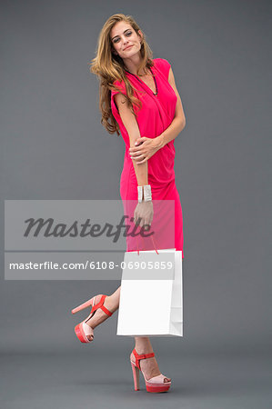 Portrait of a woman posing with a shopping bag Stock Photo - Premium Royalty-Free, Image code: 6108-06905859