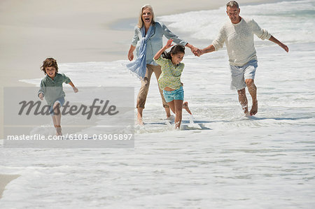Children playing with their grandparents on the beach Stock Photo - Premium Royalty-Free, Image code: 6108-06905897