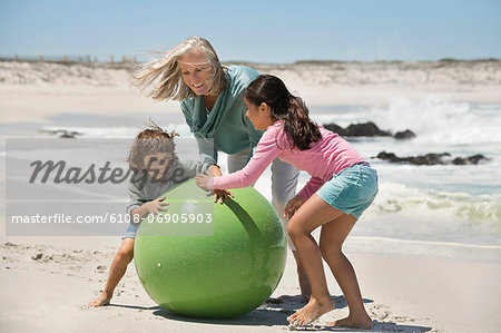 Woman playing with her grandchildren on the beach Stock Photo - Premium Royalty-Free, Image code: 6108-06905903