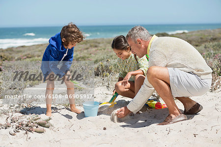 Children playing in sand with their grandfather on the beach Stock Photo - Premium Royalty-Free, Image code: 6108-06905917