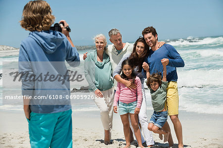 Boy filming his family with a home video camera on the beach Stock Photo - Premium Royalty-Free, Image code: 6108-06905926