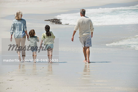 Children walking with their grandparents on the beach Stock Photo - Premium Royalty-Free, Image code: 6108-06905930