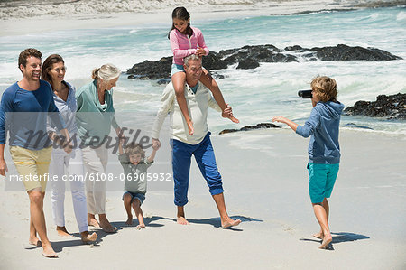 Boy filming his family with a home video camera on the beach Stock Photo - Premium Royalty-Free, Image code: 6108-06905932