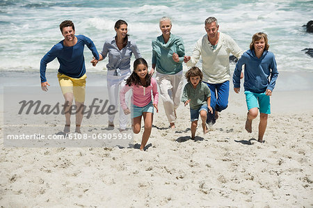 Family running on the beach Stock Photo - Premium Royalty-Free, Image code: 6108-06905936