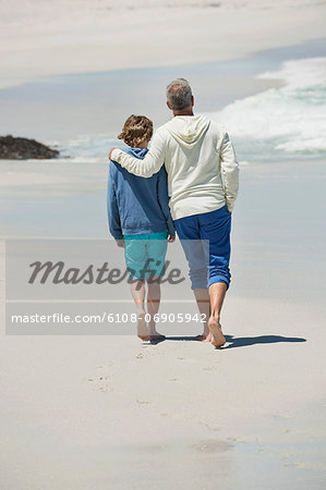 Man walking with his grandson on the beach Stock Photo - Premium Royalty-Free, Image code: 6108-06905942