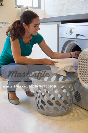 Woman doing laundry at home Stock Photo - Premium Royalty-Free, Image code: 6108-06905959