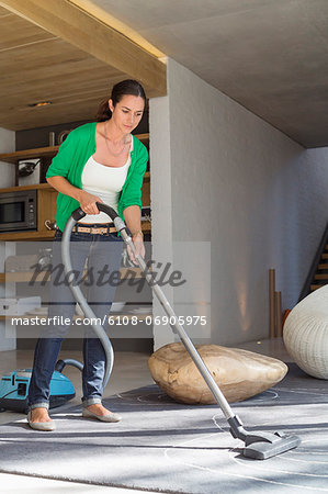 Woman cleaning house with a vacuum cleaner Stock Photo - Premium Royalty-Free, Image code: 6108-06905975