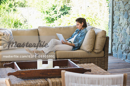 Woman reclining on a couch and using a digital tablet Stock Photo - Premium Royalty-Free, Image code: 6108-06905991
