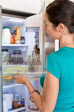 Woman putting food in a refrigerator Stock Photo - Premium Royalty-Free, Image code: 6108-06905998