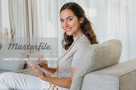 Beautiful woman using a digital tablet and smiling on a couch Stock Photo - Premium Royalty-Free, Image code: 6108-06906014