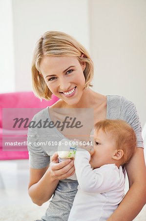 Woman feeding milk her baby with a bottle Stock Photo - Premium Royalty-Free, Image code: 6108-06906041
