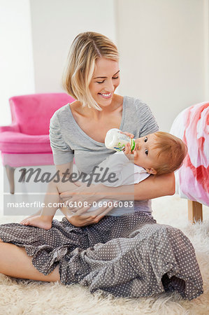 Woman feeding milk her baby with a bottle Stock Photo - Premium Royalty-Free, Image code: 6108-06906083