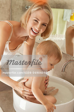 Woman giving bath to her baby in a wash bowl Stock Photo - Premium Royalty-Free, Image code: 6108-06906090