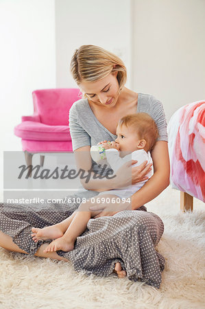 Woman sitting with her baby feeding with a baby bottle Stock Photo - Premium Royalty-Free, Image code: 6108-06906094