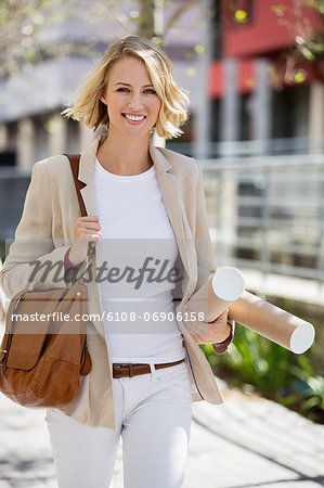 Female architect walking on a street with paper rolls Stock Photo - Premium Royalty-Free, Image code: 6108-06906158