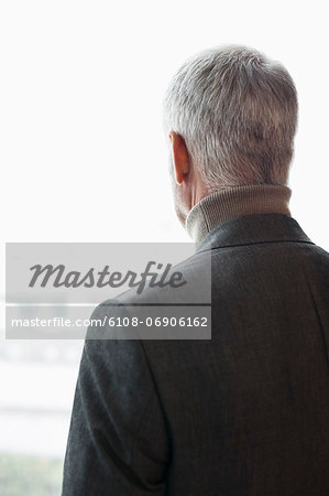 Man looking through a window Stock Photo - Premium Royalty-Free, Image code: 6108-06906162