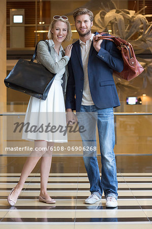 Smiling couple standing on an airport Stock Photo - Premium Royalty-Free, Image code: 6108-06906268