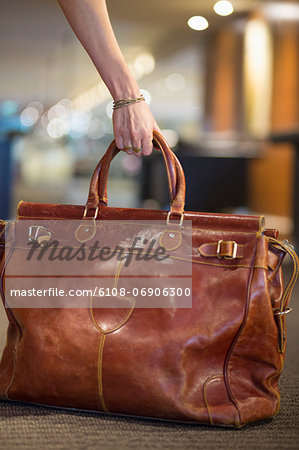 Close-up of a woman's hand picking up a leather purse Stock Photo - Premium Royalty-Free, Image code: 6108-06906300