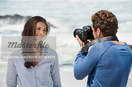 Man taking a picture of his wife with a camera on the beach Stock Photo - Premium Royalty-Free, Image code: 6108-06906316