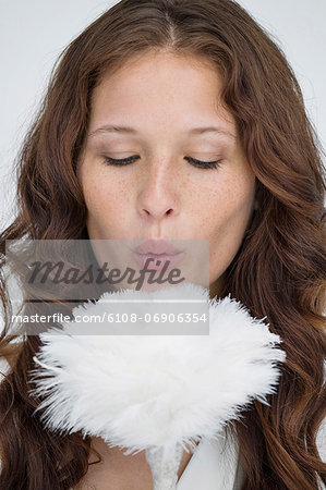 Woman blowing on a feather duster Stock Photo - Premium Royalty-Free, Image code: 6108-06906354
