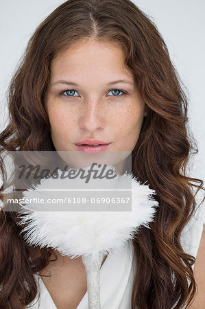 Portrait of a woman holding a feather duster Stock Photo - Premium Royalty-Free, Image code: 6108-06906367