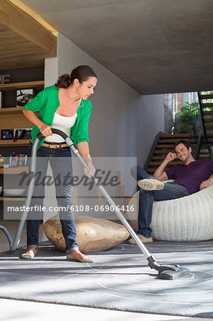 Woman cleaning house with a vacuum cleaner with her husband sitting on a seat Stock Photo - Premium Royalty-Free, Image code: 6108-06906416