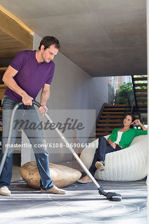 Man cleaning house with a vacuum cleaner with his wife sitting on a seat Stock Photo - Premium Royalty-Free, Image code: 6108-06906430