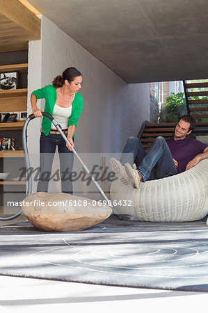 Woman cleaning house with a vacuum cleaner with her husband sitting on a seat Stock Photo - Premium Royalty-Free, Image code: 6108-06906432
