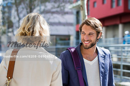 Man flirting a woman and smiling Stock Photo - Premium Royalty-Free, Image code: 6108-06906517