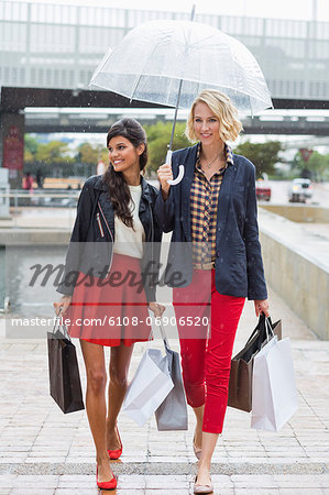 Female friends walking with shopping bags and smiling Stock Photo - Premium Royalty-Free, Image code: 6108-06906520