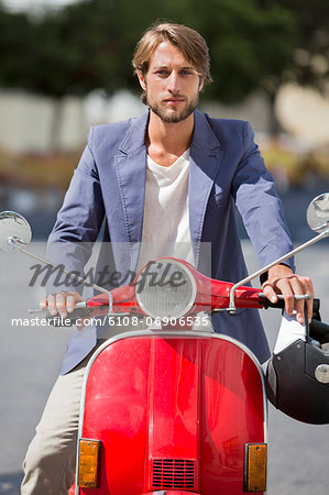 Man riding a scooter Stock Photo - Premium Royalty-Free, Image code: 6108-06906535