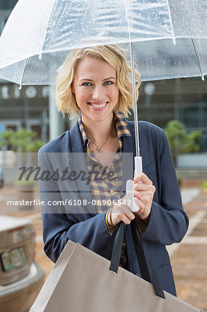 Portrait of a smiling woman with an umbrella Stock Photo - Premium Royalty-Free, Image code: 6108-06906542