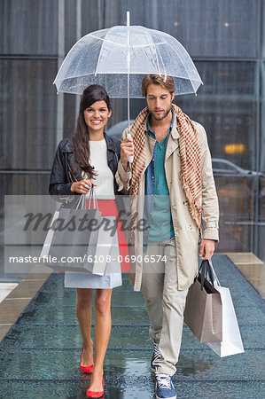 Couple with shopping bags sheltering under umbrella in rain Stock Photo - Premium Royalty-Free, Image code: 6108-06906574