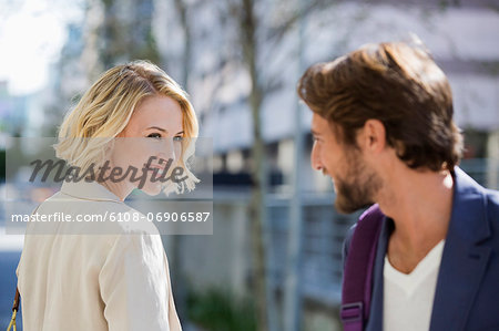 Man and woman smiling at each other Stock Photo - Premium Royalty-Free, Image code: 6108-06906587