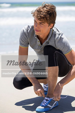 Man tying his shoelaces on the beach Stock Photo - Premium Royalty-Free, Image code: 6108-06906665