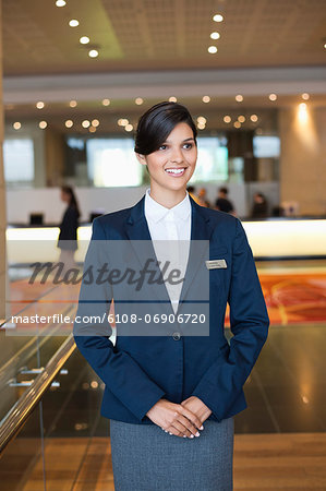 Receptionist standing in a hotel lobby and smiling Stock Photo - Premium Royalty-Free, Image code: 6108-06906720
