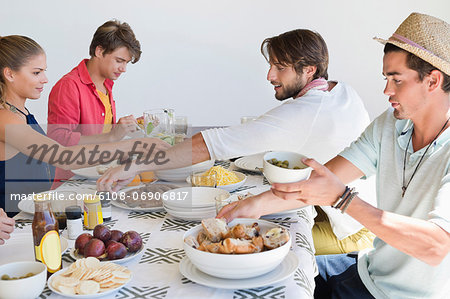 Friends eating lunch at dining table Stock Photo - Premium Royalty-Free, Image code: 6108-06906817